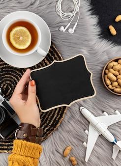 La main de la femme dans un pull avec un ancien avion appareil photo instantané et du thé.