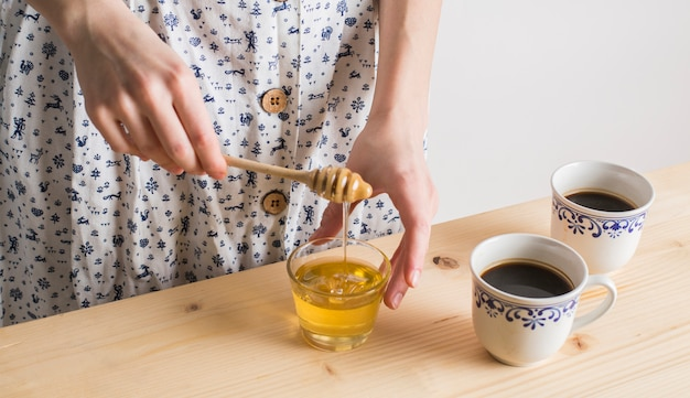 Main de femme dégoulinant de miel dans un verre avec une tasse de thé sur un bureau en bois