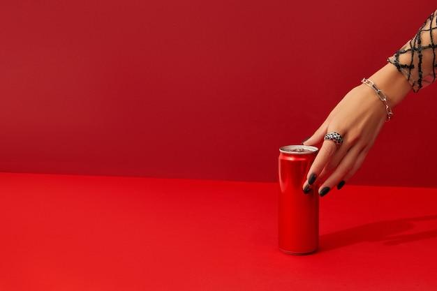 La main de la femme avec un design d'ongle effrayant prend une boîte sur fond rouge au soleil