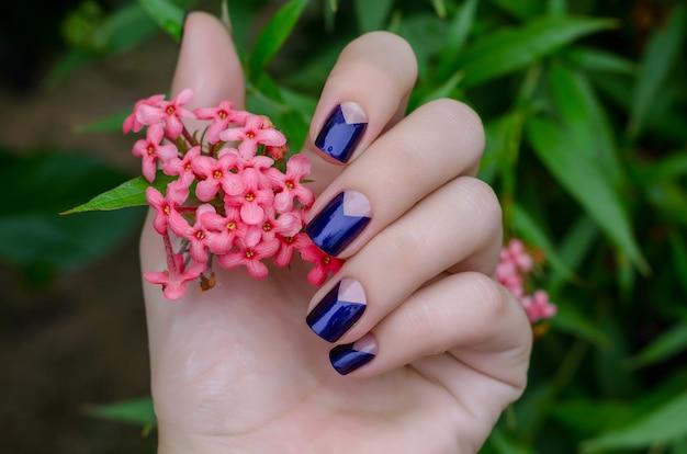 Main de femme avec un design d'ongle violet étincelant