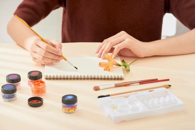 Main de femme avec dessin au pinceau sur le bloc-notes. processus de création de la peinture à l'aquarelle