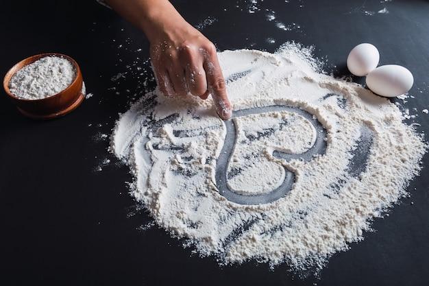 La main d'une femme dessine un cœur sur la farine, cuisinant avec amour.