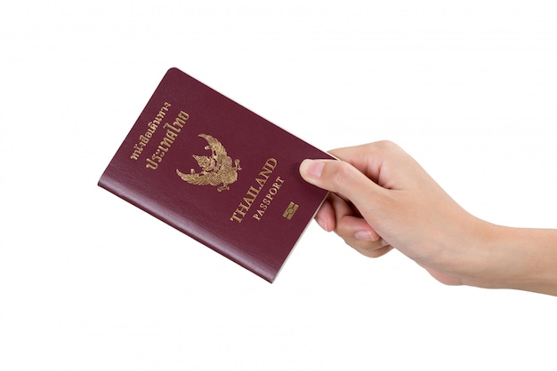 Main de femme détenant un passeport thaïlandais isolé sur blanc