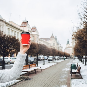 La main de la femme détient une tasse de papier rouge avant l'allée de la vieille ville