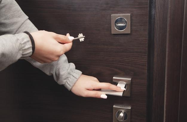 Main de femme déverrouillage de la porte avec clé.