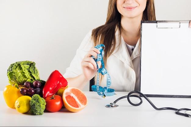 Main de femme diététicien tenant presse-papiers vierge et ruban à mesurer en clinique