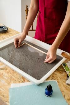 Main de femme dissolvant la moisissure dans la pâte à papier pour faire du papier