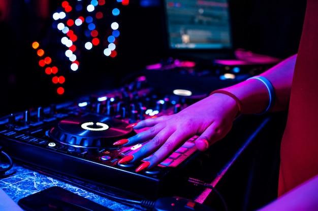 Main d'une femme dj avec une table de mixage de contrôleur de musique