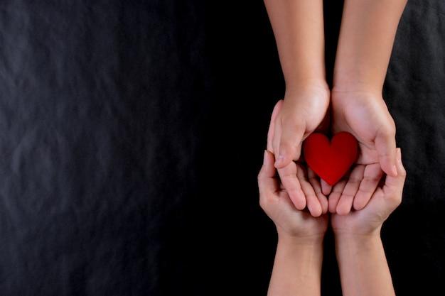 Main de femme donnant un coeur rouge à l'enfant. journée internationale du concept de charité. copiez l'espace.