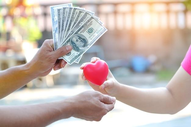 Main de femme donnant le symbole du coeur rouge avec l'échange d'argent de quelqu'un