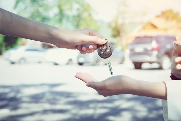 La main de la femme donne la clé de la voiture et l'arrière-plan flou.
