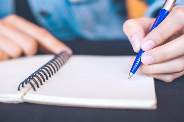 Main de femme écrit sur un bloc-notes avec un stylo dans le bureau.