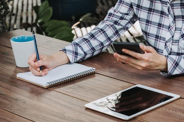 Main de femme écrit le bloc-notes et tenant le téléphone sur la table en bois au café