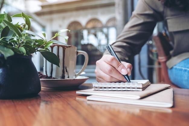 Main de femme écrit sur un cahier vierge avec une tasse de café sur une table en bois