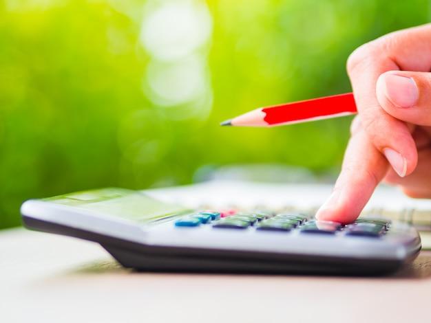 Main de femme écrit avec un crayon rouge, un document commercial et un carnet de notes sur une table de travail