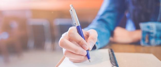 Une main de femme écrit dans le bloc-notes en spirale vide avec un stylo. bannière web