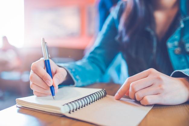 La main d'une femme écrit dans un bloc-notes en spirale vide avec un stylo.