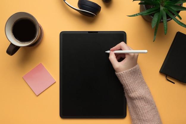 La main d'une femme écrit dans une tablette numérique maquette