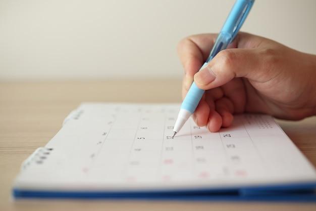 Main de femme écrit sur la date du calendrier