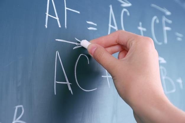 Main de femme écrit des formules sur tableau noir avec de la craie se bouchent