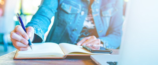 Main de femme écrivant sur le bloc-notes avec un stylo