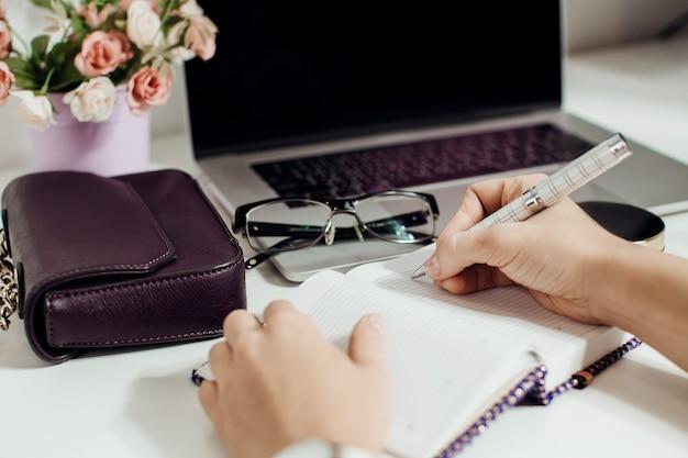Main de femme écrivant dans un bloc-notes vide placé sur un bureau avec un ordinateur portable, des lunettes, un pot de fleurs