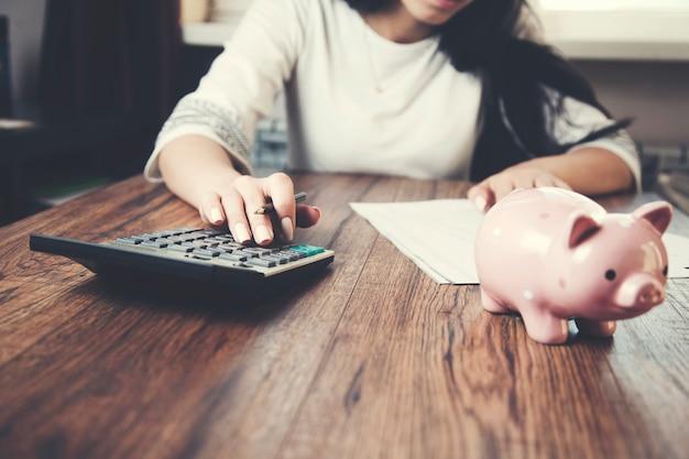 Main de femme écrivant dans des documents et utilisant la calculatrice