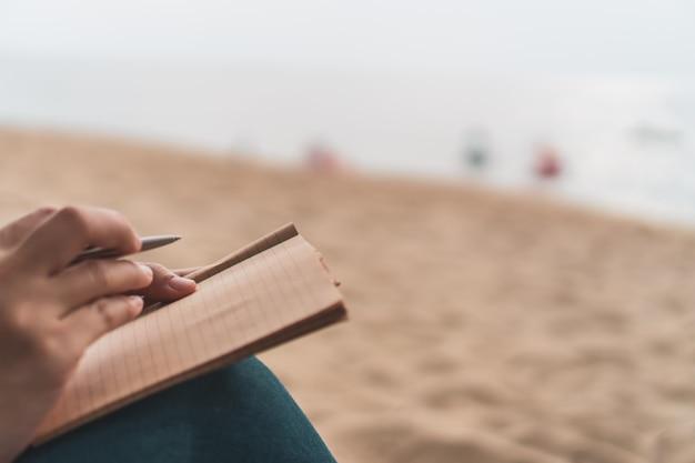 Main de femme écrivant dans un petit carnet blanc.