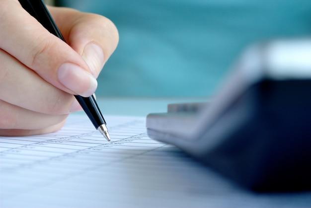 Main de femme écrivant des entrées dans un cahier