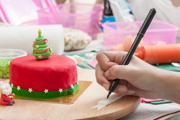 Main de femme écrivant sur fondant avec stylo de qualité alimentaire