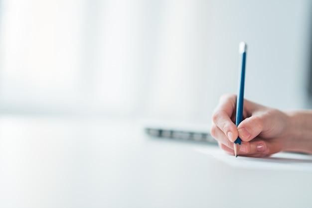 Main d'une femme écrivant sur papier.