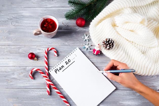 Main de femme écrivant des vœux de noël