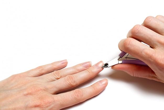 Main de femme enlever la cuticule des ongles sur un tableau blanc clair.