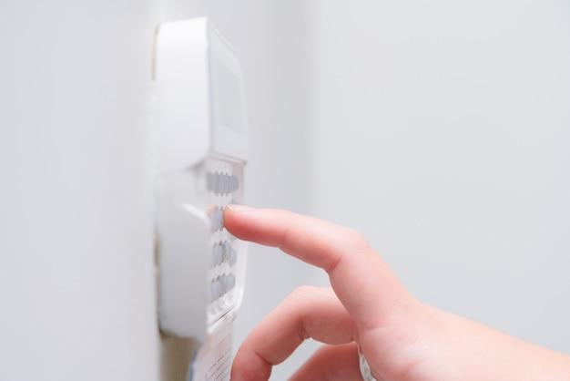 Main de femme entrant le mot de passe du système d'alarme d'un appartement, maison de bureau d'affaires. console de surveillance et de protection contre caoutchouteux et voleur