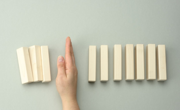 La main d'une femme entre les blocs de bois en empêche la plupart de tomber. le concept d'assurance, un leader fort qui empêche l'entreprise de faire faillite