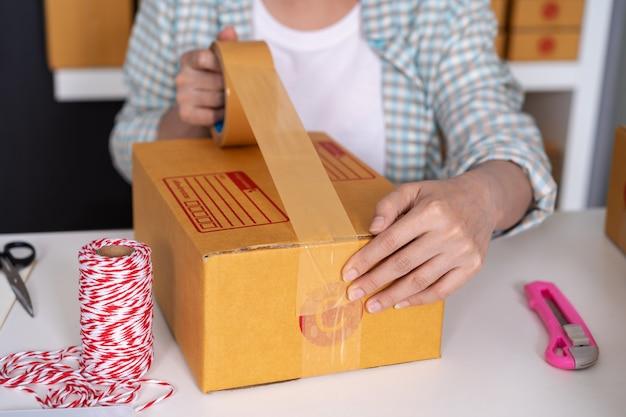Main de femme entrepreneur en ligne avec du ruban adhésif pour emballer une boîte à colis à la maison