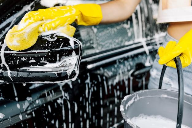 La main d'une femme avec une éponge jaune pour se laver, laver une voiture.