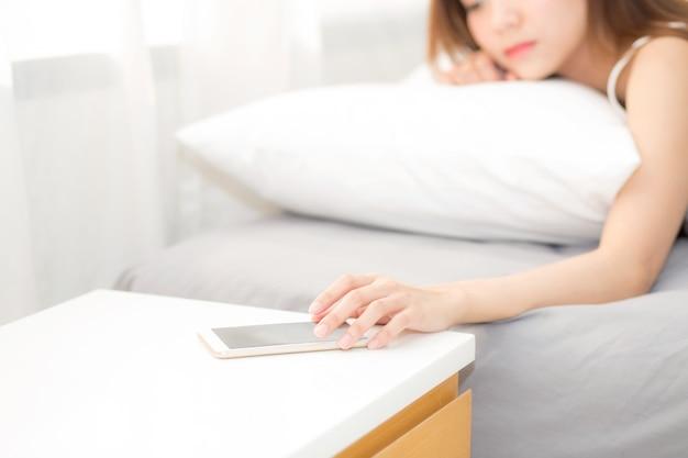 Main de la femme éteindre l'alarme sur appel téléphone mobile tout en se réveillant après le sommeil se détendre.