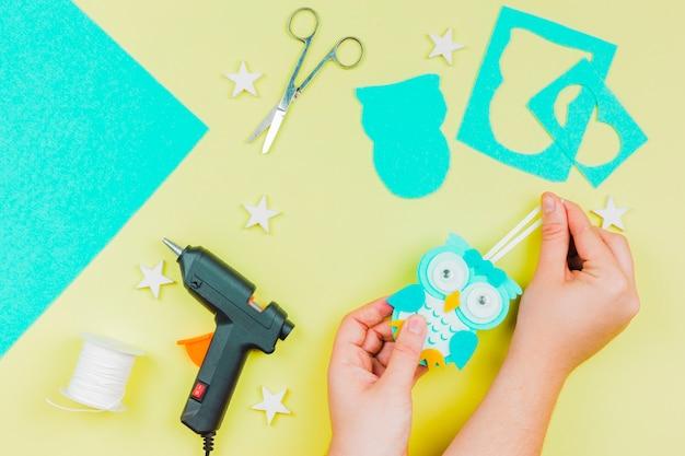 Main de femme faisant accrocher un hibou de mur de papier peint sur fond coloré