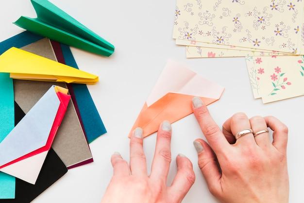 Main de femme faisant un avion en papier sur fond blanc