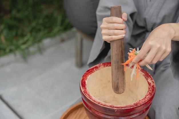 La main d'une femme faisant de la nourriture thaïlandaise appelle une salade de papaye ou som tam, mélangeant et martelant dans un mortier.
