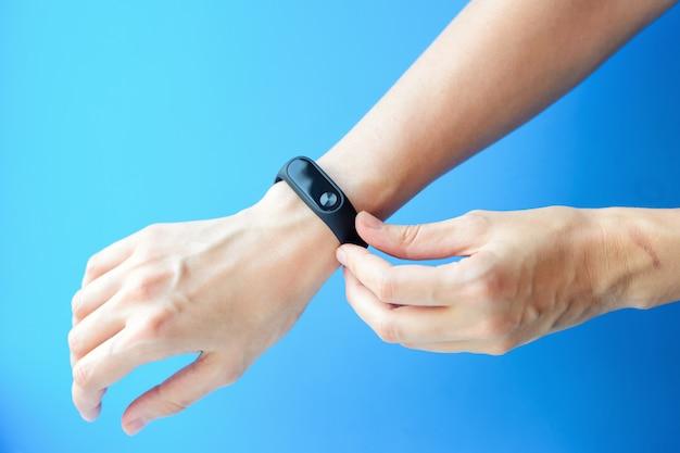 Main de femme avec fitness trecker sur fond bleu