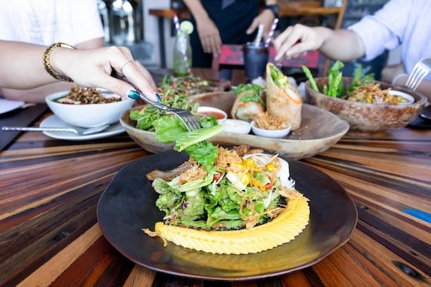 Main de femme avec une fourchette en mangeant une salade de légumes avec des amis