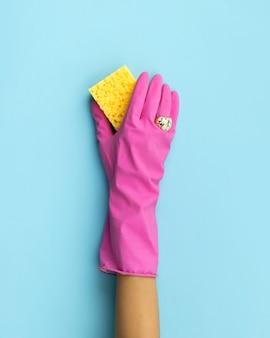Main de femme en gant en caoutchouc rose laver par fond bleu éponge. service de nettoyage ou mise en page créative de ménage.