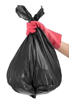 Main de femme avec un gant rouge tenant un sac poubelle complet isolé sur blanc
