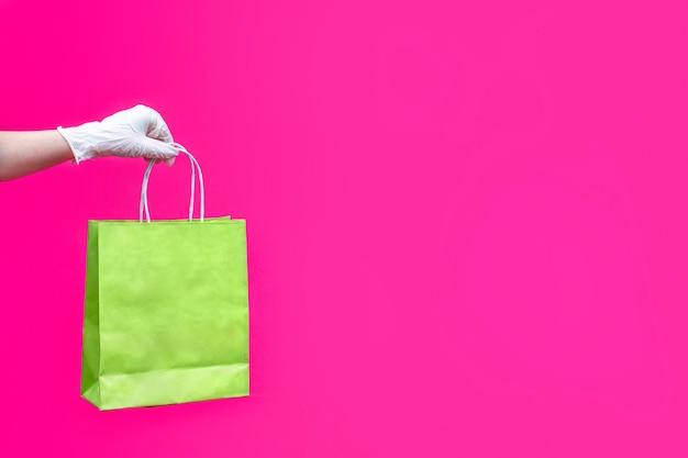 Main de femme en gant avec sac en papier rose.