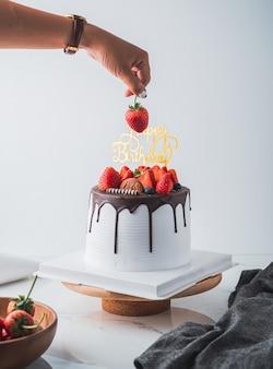 Main de femme et gâteau aux fruits frais d'anniversaire avec du chocolat joyeux anniversaire sur le gâteau