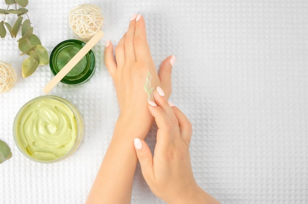 Main de femme avec un gel d'aloe vera sur le doigt au-dessus d'un pot de crème hydratante cosmétique et de feuilles vertes sur fond blanc, composition vue de dessus