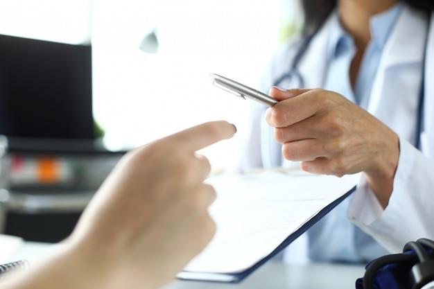 Main de femme gp passant au patient stylo argenté