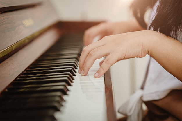Main de femme gros plan jouant du piano à la maison colortone vintage.